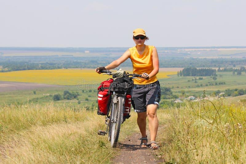 Menina com uma bicicleta e uma trouxa que anda ao longo da estrada