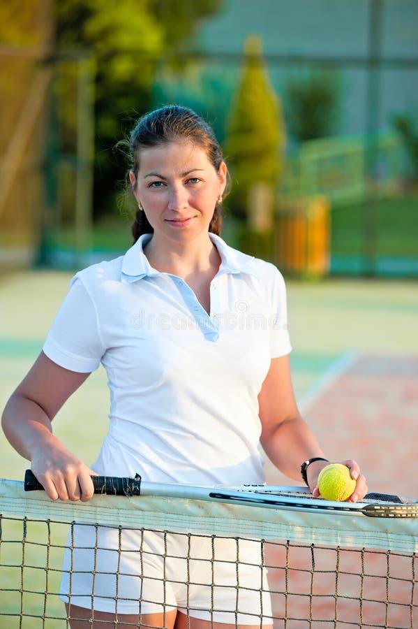 Menina com uma bola e uma raquete de tênis no valor líquido foto de stock royalty free