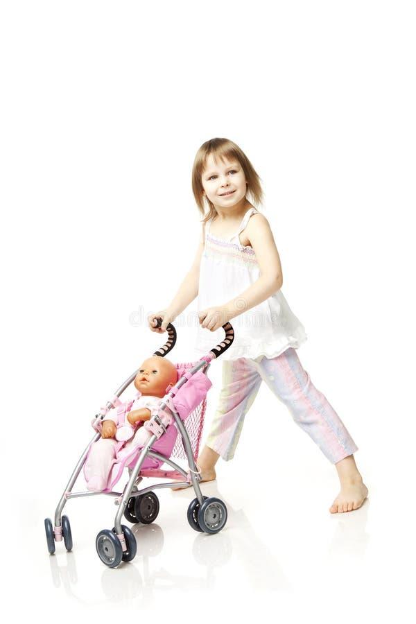Menina com uma boneca no pram imagem de stock