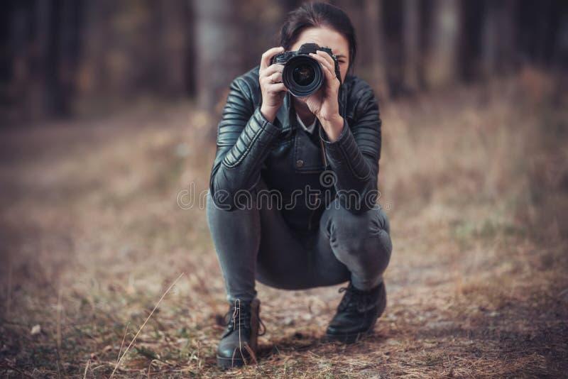 Menina com uma câmera de SLR em um revestimento preto fotos de stock royalty free