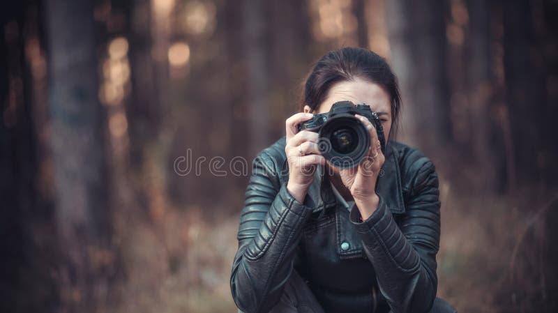 Menina com uma câmera de SLR em um revestimento preto fotografia de stock
