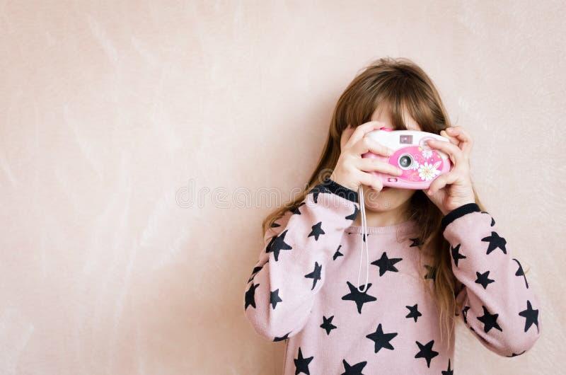 A menina com uma c?mera cor-de-rosa da foto imagens de stock royalty free