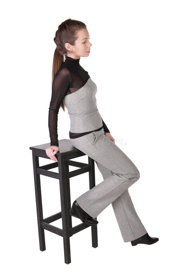 A menina com uma cadeira da barra imagem de stock