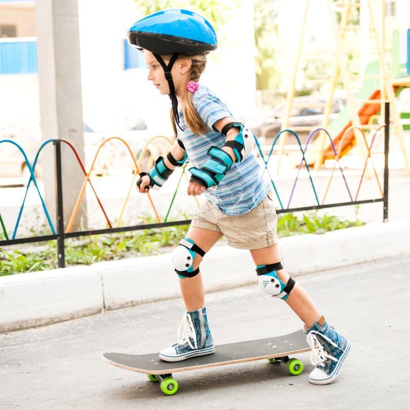 Menina com uma equitação do capacete no skate foto de stock