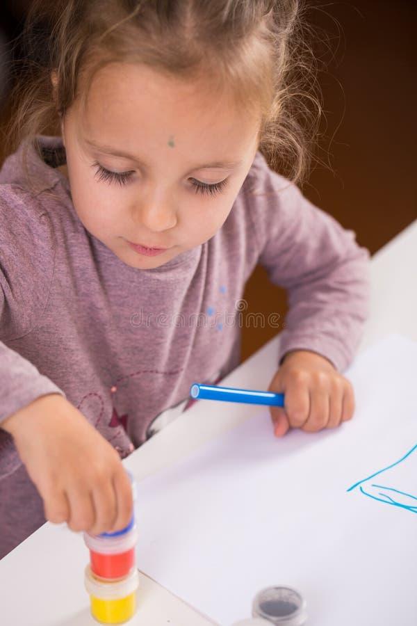 Menina com uma escova e pinturas imagem de stock royalty free
