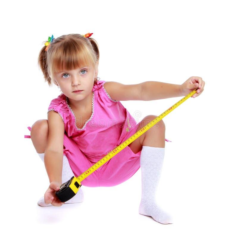 Menina com uma fita m?trica de constru??o fotos de stock royalty free