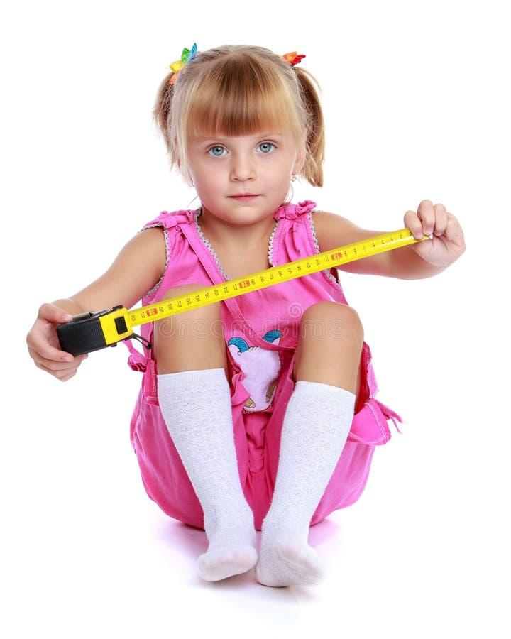 Menina com uma fita m?trica de constru??o imagens de stock royalty free