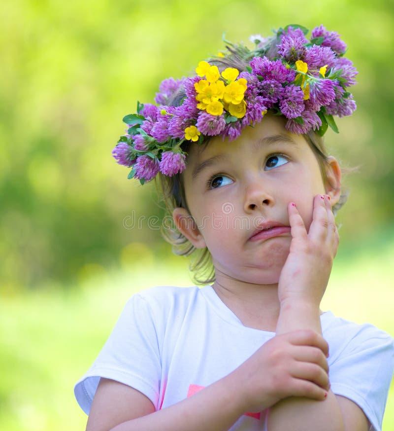 Menina com uma grinalda das flores em sua cabeça imagem de stock