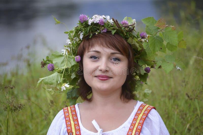 Menina com uma grinalda das folhas em sua cabeça imagem de stock