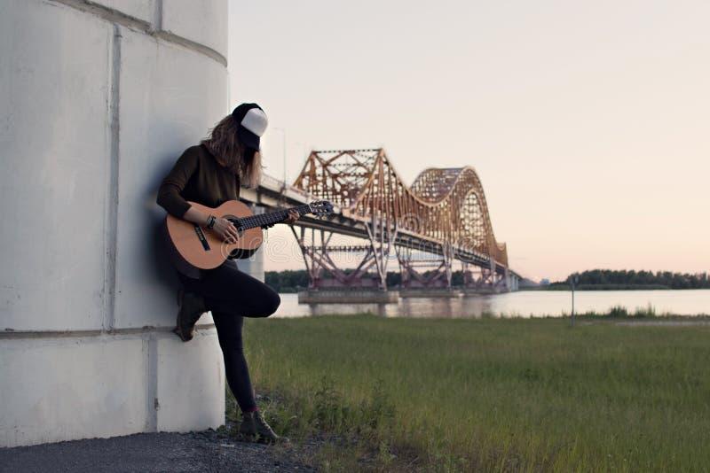 Menina com uma guitarra que está no pé da ponte sobre o r foto de stock royalty free