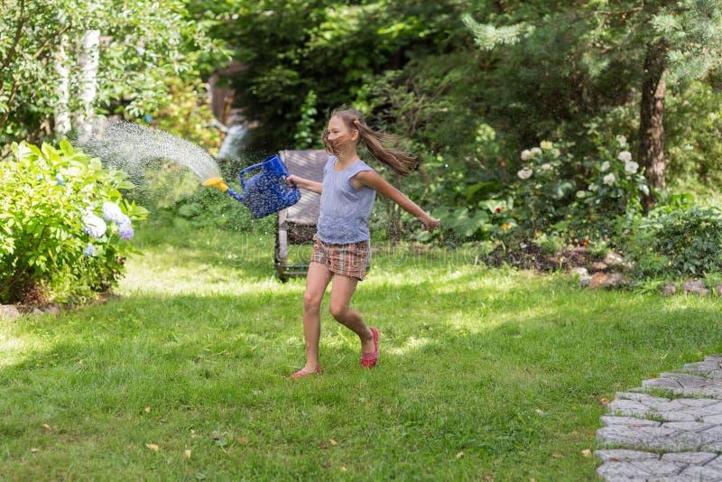 Menina com uma lata molhando no verão fotografia de stock