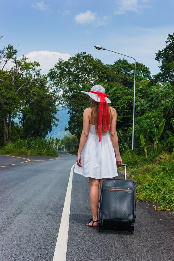 Menina com uma mala de viagem em uma estrada abandonada imagens de stock
