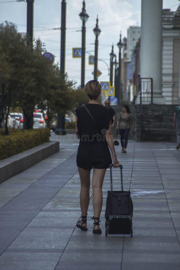 Menina com uma mala de viagem na cidade Omsk imagens de stock royalty free