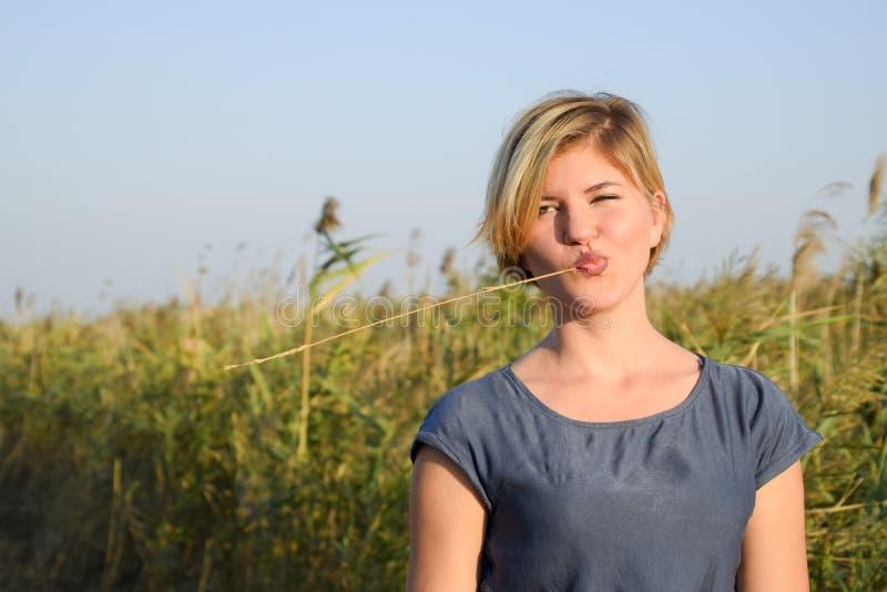 Menina com uma palha em sua boca contra um fundo de arvoredos de lingüeta imagens de stock royalty free