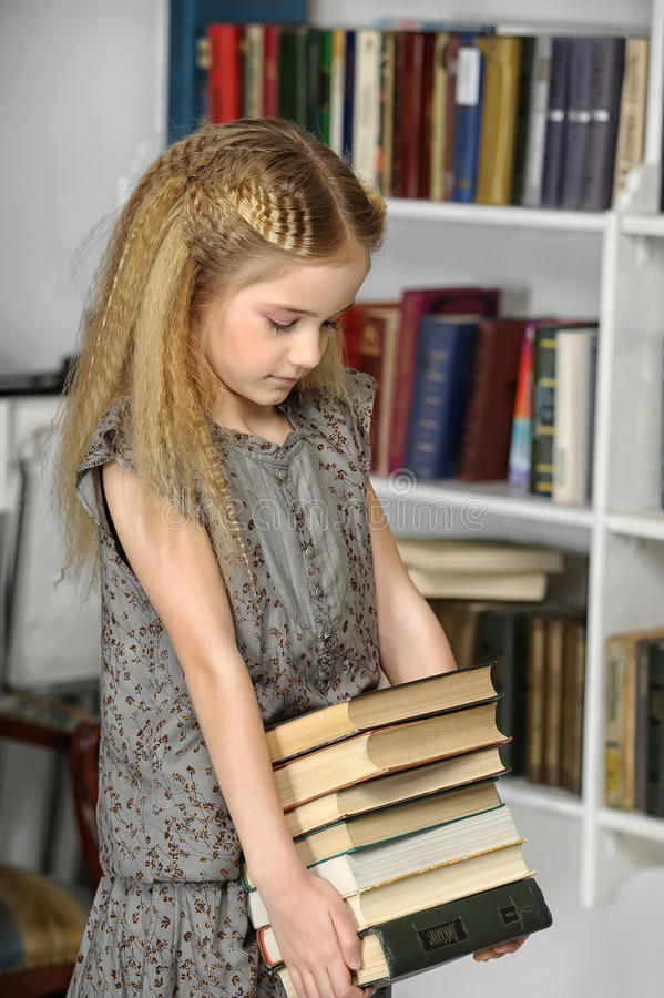 Menina com uma pilha dos livros imagens de stock