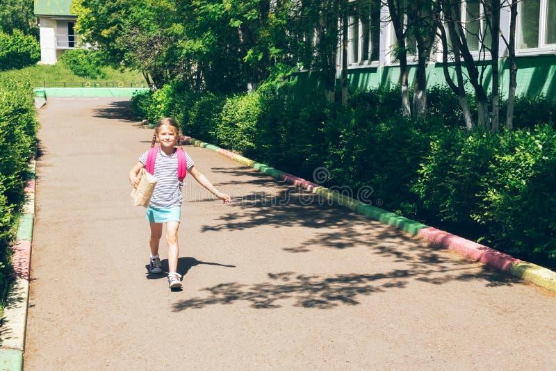 A menina com uma trouxa cor-de-rosa e um saco de papel com uma mordida vai educar Conceito da escola Quadro horizontal imagem de stock royalty free