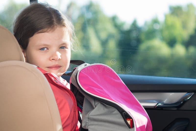 A menina com uma trouxa em um banco de carro da criança monta no carro à escola fotos de stock