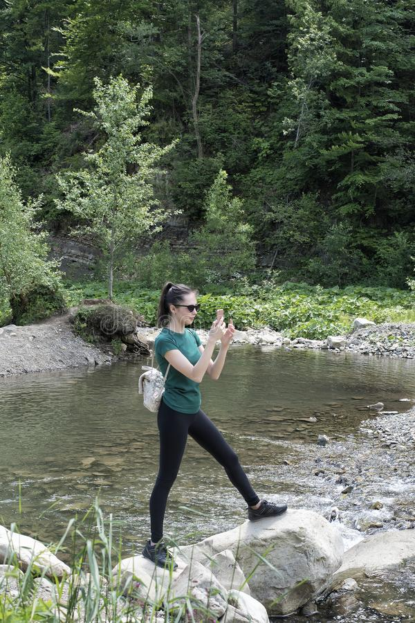 A menina com uma trouxa está no banco de rio e toma uma foto imagens de stock royalty free