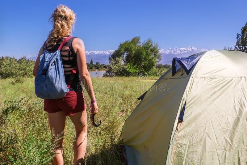 A menina com uma trouxa está perto de uma barraca e olha o lago e um iate pequeno imagens de stock royalty free