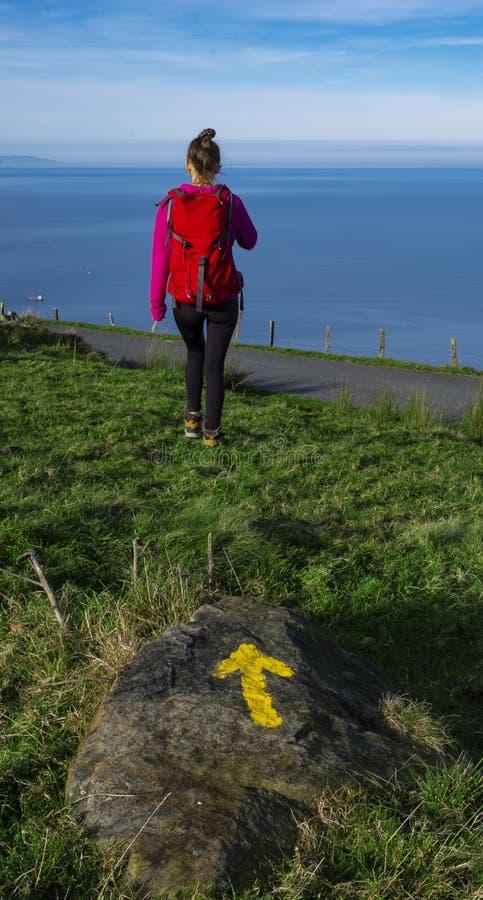 Menina com uma trouxa na montagem com uma seta do camino do norte de Santiago da estrada de Satiago imagem de stock royalty free
