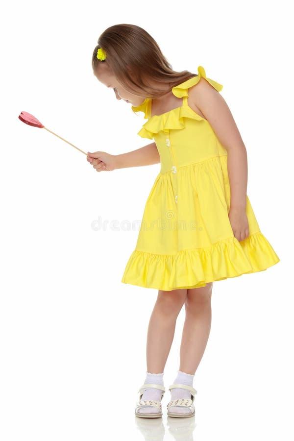Menina com uns doces em uma vara imagens de stock