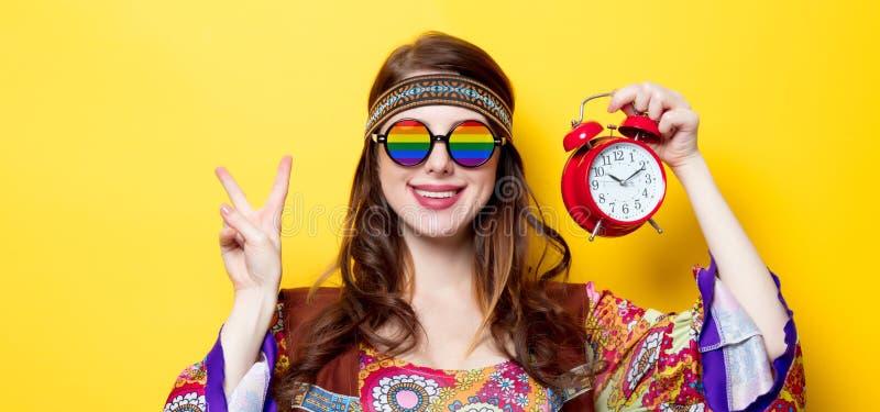 Menina com vidros e despertador do arco-íris imagem de stock royalty free