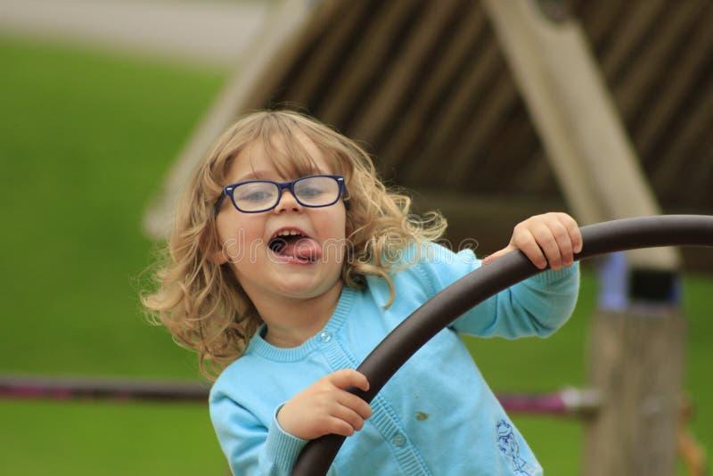 A menina com vidros e uma camisa azul que joga em um campo de jogos na escola envelheceram 3 a 5 imagem de stock