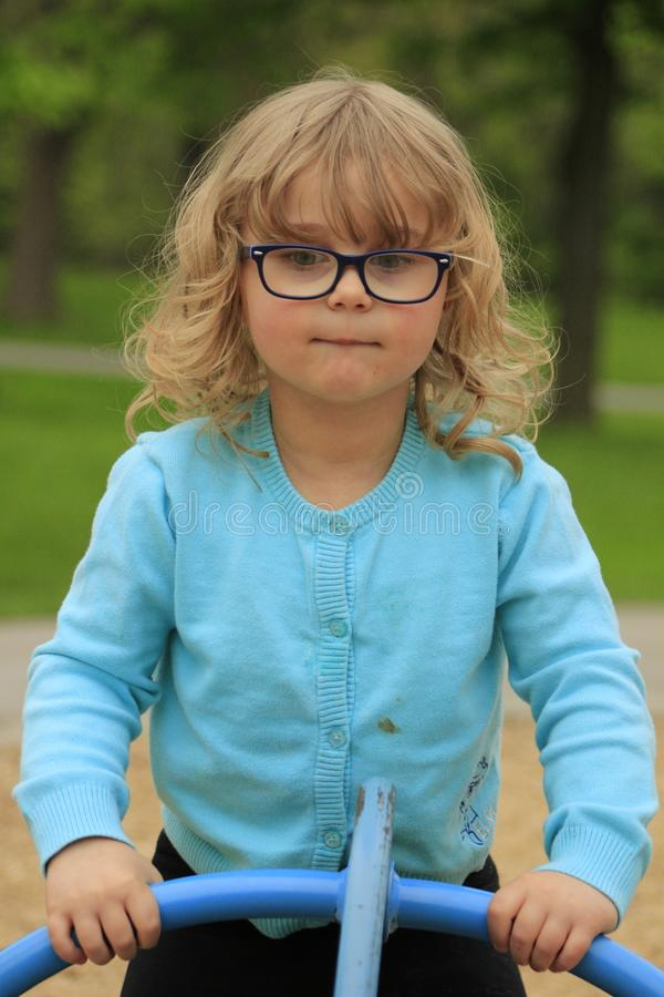 A menina com vidros e uma camisa azul que joga em um campo de jogos na escola envelheceram 3 a 5 fotografia de stock