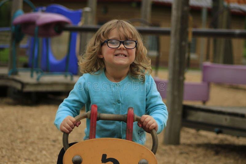 A menina com vidros e uma camisa azul que joga em um campo de jogos na escola envelheceram 3 a 5 foto de stock