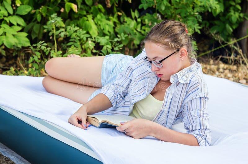 Menina com vidros que lê um livro, encontrando-se em um colchão de ar nas madeiras imagem de stock