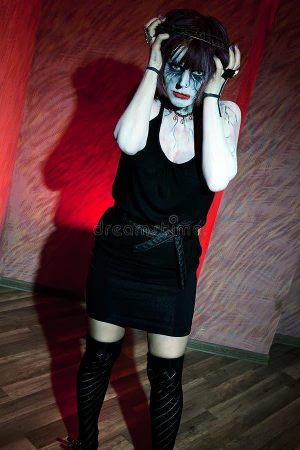 A menina com zombi compõe na parede vermelha imagem de stock