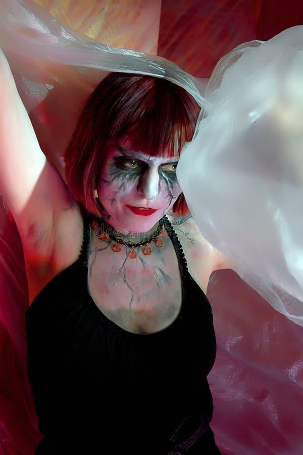 A menina com zombi compõe na parede vermelha imagens de stock royalty free