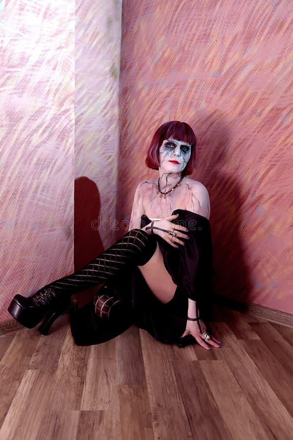 A menina com zombi compõe na parede vermelha fotografia de stock royalty free