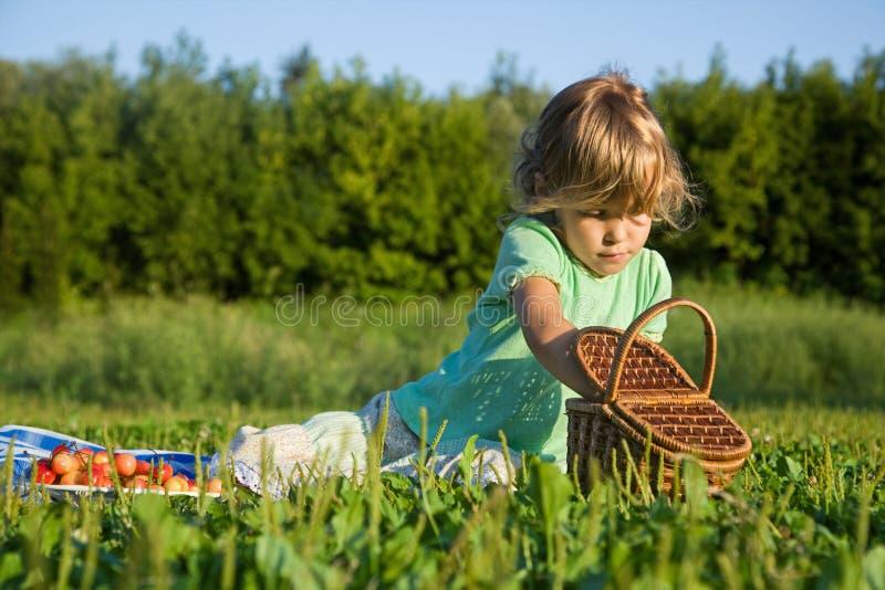 A menina começ das cerejas doces da cesta fotografia de stock