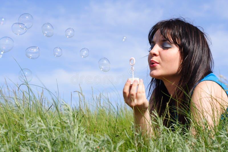 A menina começa acima bolhas de sabão imagem de stock