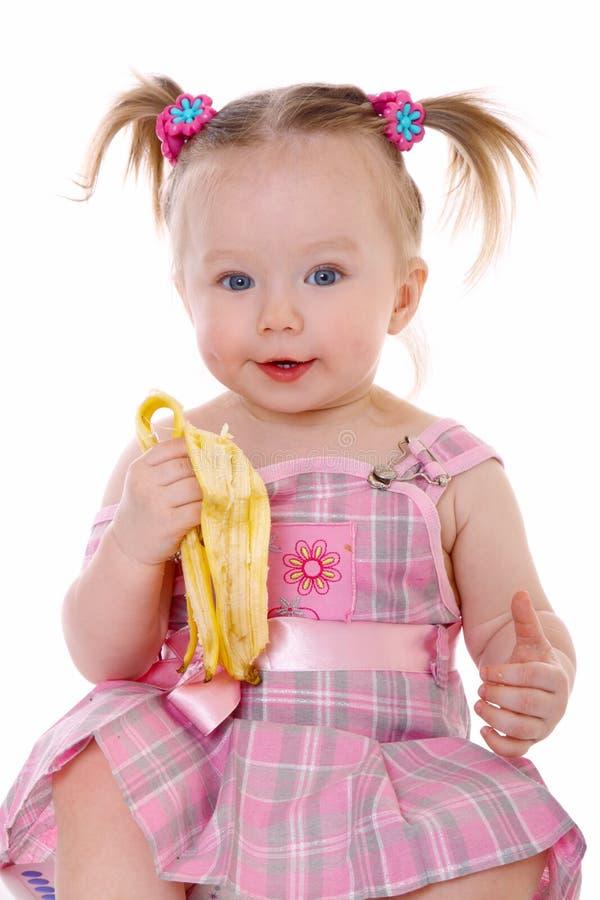 A menina come a banana imagens de stock royalty free