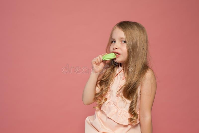 A menina come o bolo doce com queque de creme fotos de stock royalty free