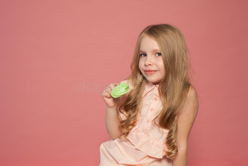 A menina come o bolo doce com queque de creme imagens de stock royalty free