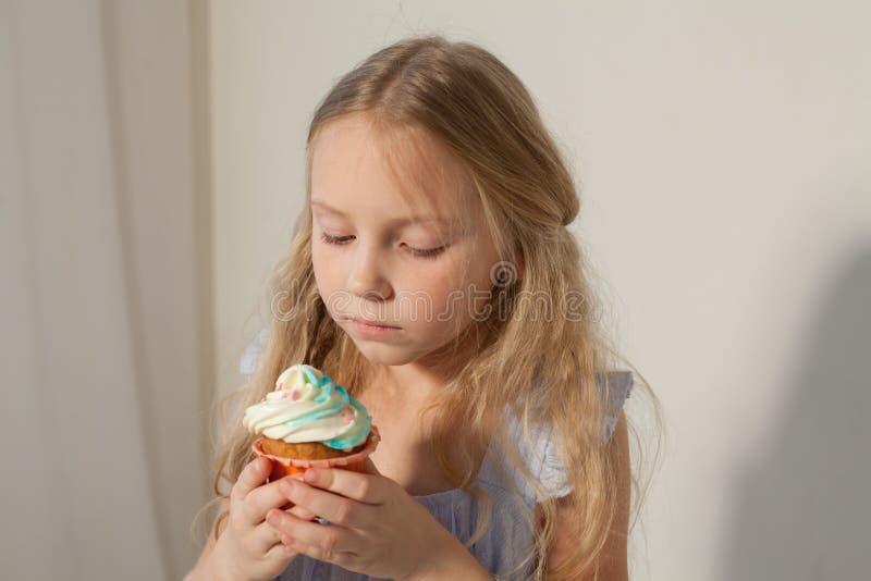 A menina come o bolo doce com queque de creme fotografia de stock