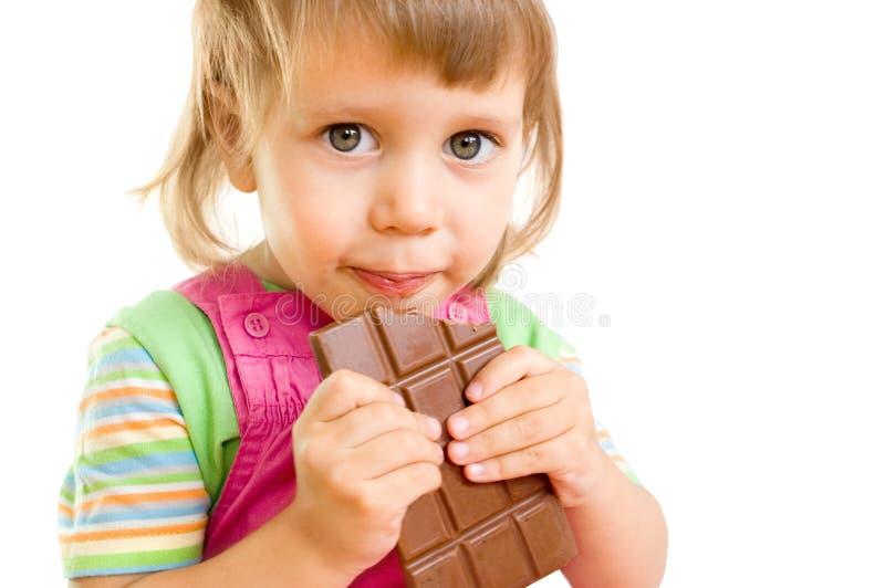 A menina come o chocolate fotografia de stock