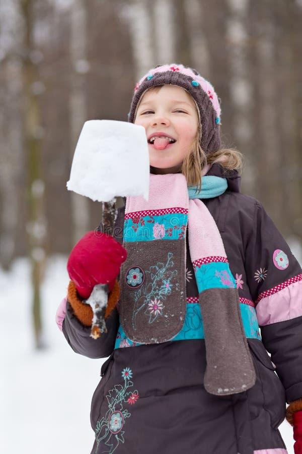 A menina come o esquimó feito da parte de neve imagens de stock