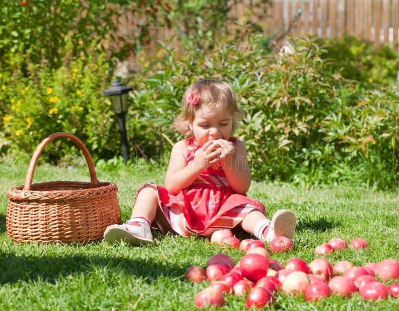 A menina come uma maçã imagem de stock