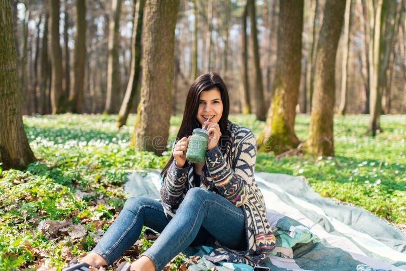Menina comendo saudável feliz que bebe a desintoxicação verde do batido fora na madeira fotos de stock royalty free