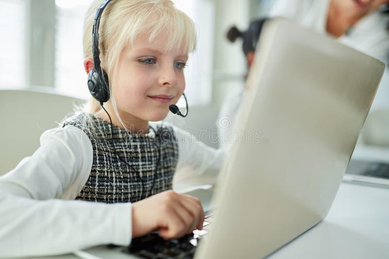 Menina como um estudante com os auriculares durante o ensino eletrónico foto de stock royalty free