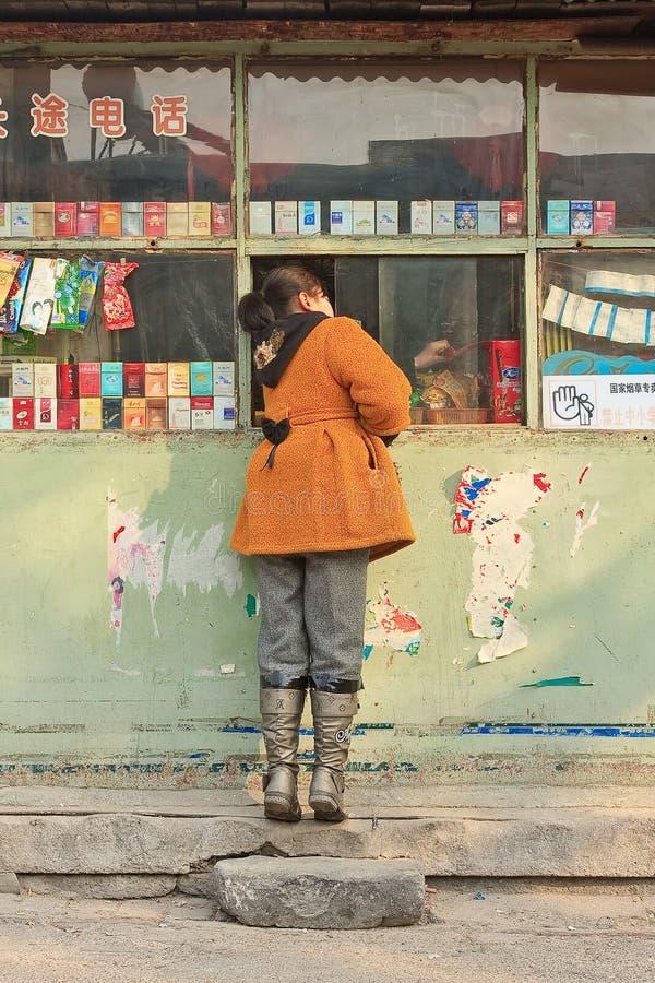 A menina compra doces em uma loja de vizinhança, Pequim, China imagem de stock royalty free
