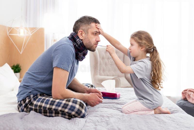 Menina concentrada que trata seu pai doente fotografia de stock