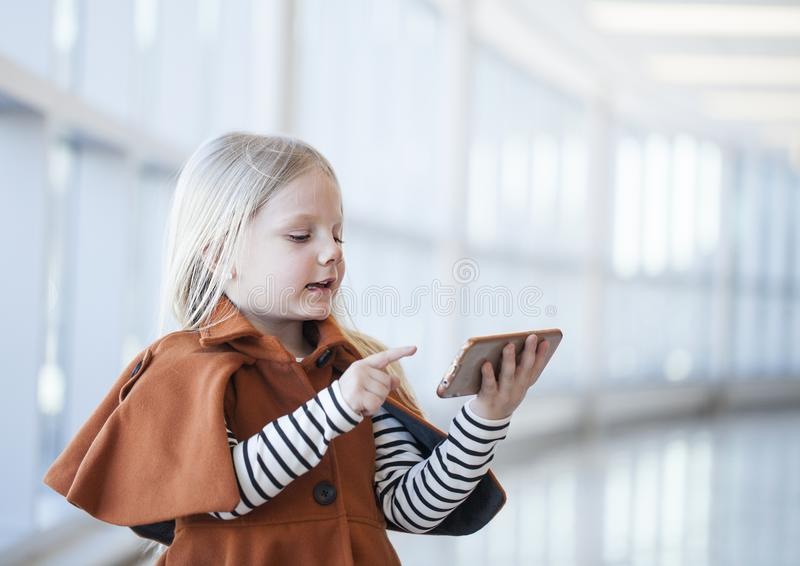 Menina concentrada que veste o revestimento alaranjado que joga o smartphone imagem de stock royalty free