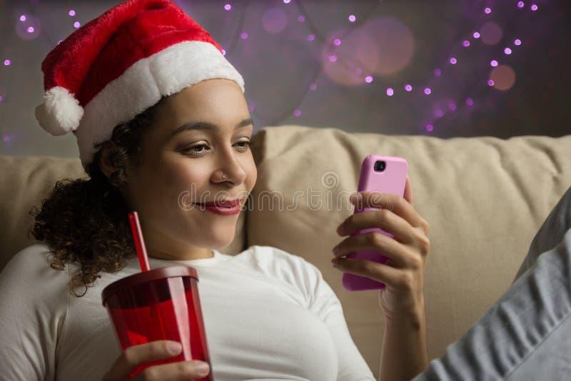 Menina confortável da raça misturada com o chapéu do Natal que olha a pilha p foto de stock