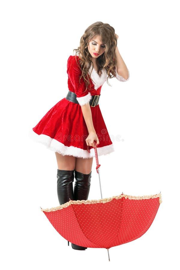 Menina confundida bonito de Santa com o guarda-chuva e a cabeça do risco que olham para baixo imagem de stock