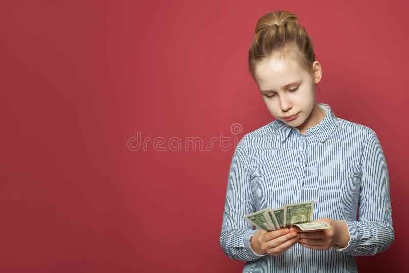 A menina confundida infeliz nova que guarda um dólares americanos desconta o dinheiro no fundo cor-de-rosa fotos de stock